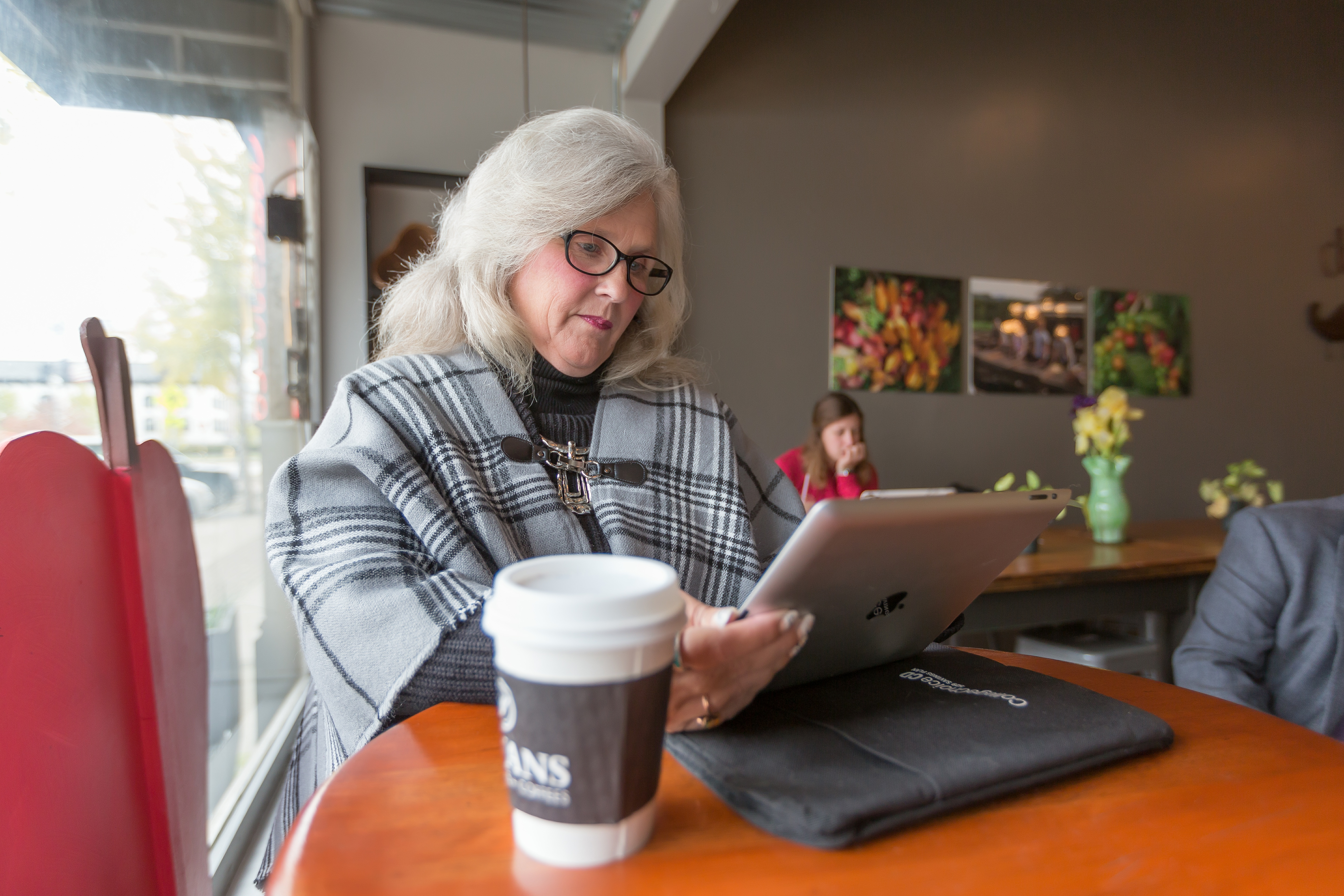 Woman in coffee shop on tablet